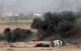 Palestinian protesters take cover during clashes with Israeli troops along Gaza's border with Israel, east of Khan Younis, Gaza Strip, Thursday, April 5, 2018.  An Israeli airstrike in northern Gaza early on Thursday killed a Palestinian, while a second man died from wounds sustained in last week's mass protest. The fatalities bring to 21 the number of people killed in confrontations in the volatile area over the past week with a new round of protests along the border is expected on Friday. (AP Photo/Adel Hana)